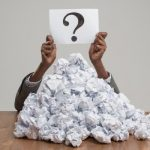 Person sitting with a mountain of crumpled paper in front of them